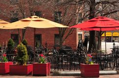Outdoor Dining at a Cafe. Restaurant tables set up on a sidewalk under umbrellas stock image