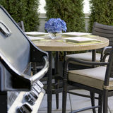 Outdoor Dining Entertaining BBQ. Outdoor patio table and stainless steel BBQ royalty free stock image
