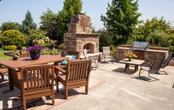 Outdoor kitchen with garden 2. A custom fireplace feature with  BBQ, granite counters and an organic garden reflect todays homeowners needs Royalty Free Stock Photos