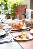 Outdoor dining meal complete with roast chicken. Salad, bread rolls, wine and fruit in summer. Concept of outdoor dining Royalty Free Stock Photos