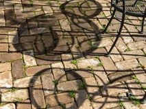 Outdoor dining, shadows on the pavers. Shadows on brick pavers, outdoor dining area royalty free stock photo