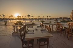 Outdoor dining table with sunset in tropical hotel resort. Outdoor dining terrace area with table set up on tropical ocean beach of luxury hotel resort at dusk stock image