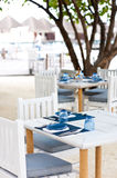 Outdoor dining tables on the sand beach Stock Photography