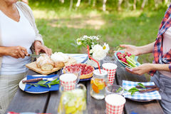 Outdoor dinner. Two women serving table for picnic outdoors Stock Image