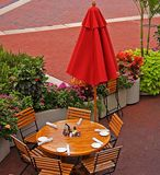 Outdoor Eatery. This shot is a beautiful inviting outdoor eatery just waiting for people to come and sit beneath the red umbrellas and beautiful brickwork and Royalty Free Stock Photo