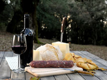 Outdoor eating with bread, cheese, sausage and red wine. Stock Image