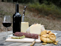 Outdoor eating with bread, cheese, sausage and red wine. Royalty Free Stock Photography
