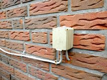 Outdoor electrical socket is mounted on the brick wall stock images