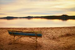 Outdoor empty bench on autumn lake beach. The coast with shining sun. Vintage toned photo Stock Images
