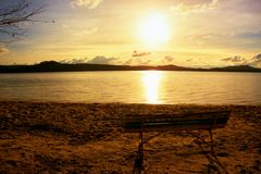 Outdoor empty bench on autumn lake beach. The coast with sunset. Vintage toned photo with lens flare effect Royalty Free Stock Photos