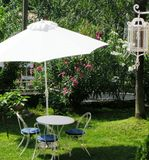 Outdoor entertaining. Outdoor entertainment area with chairs table and umbrella in blue and white with a pretty garden and lantern for a garden wedding or Stock Photos