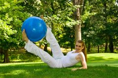 Outdoor exercise. Fitness girl outdoor exercise by pilates ball royalty free stock image