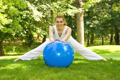 Outdoor exercise. Fitness girl outdoor exercise by pilates ball stock photo