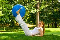 Outdoor exercise. Fitness girl outdoor exercise by pilates ball stock images