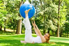 Outdoor exercise. Fitness girl outdoor exercise by pilates ball royalty free stock images