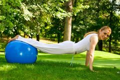 Outdoor exercise. Fitness girl outdoor exercise by Pilate's ball stock images