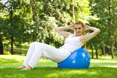 Outdoor exercise. Fitness girl outdoor exercise by Pilate's ball stock image