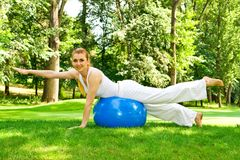 Outdoor exercise. Fitness girl outdoor exercise by Pilate's ball stock photos