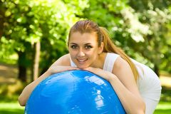 Outdoor exercise. Fitness girl outdoor exercise by Pilate's ball stock photo