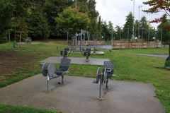 Outdoor exercise equipment mounted on concrete pads. Including cycling and rowing equipment, bench, cycle, day, forest, grass, green, lawn, machine, nobody royalty free stock image
