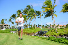 Outdoor exercise man running on grass in city park Stock Photos