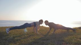Outdoor exercise, sports couple in love simultaneously doing push-ups during sunset on mountain against a beautiful. Outdoor exercise, sports couple in love stock video