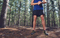 Outdoor exercise watch. Man looking at stopwatch to check gps pace and time on trail run Stock Photo