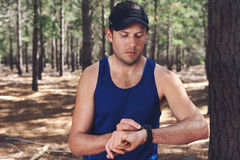Outdoor exercise watch. Man looking at stopwatch to check gps pace and time on trail run Royalty Free Stock Image