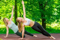 Outdoor exercise, yoga classes with an individual. Trainer stock photo
