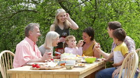 Outdoor Family Meal. Family are sitting outdoors in summer to have a picnic meal