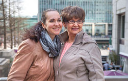 Outdoor family portrait of pension age Mother and her daughter in the city, smiling and looking around. Two generation, happiness Royalty Free Stock Photography