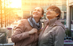 Outdoor family portrait of pension age Mother and her daughter in the city, smiling and looking around. Two generation, happiness Stock Photo