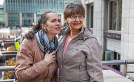 Outdoor family portrait of pension age Mother and her daughter in the city, smiling and looking around. Two generation, happiness Royalty Free Stock Image