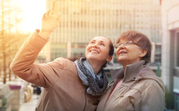 Outdoor family portrait of pension age Mother and her daughter in the city, smiling and looking around. Two generation, happiness Royalty Free Stock Photo