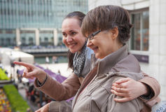 Outdoor family portrait of pension age Mother and her daughter in the city, smiling and looking around. Two generation, happiness Royalty Free Stock Images