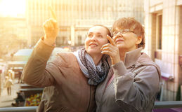 Outdoor family portrait of pension age Mother and her daughter in the city stock image