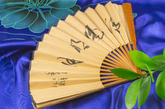 Outdoor fan and green stems lying on the blue silk Royalty Free Stock Photos