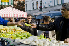 Outdoor farmers market, man buying peppers. Farmers market day outdoors, a vegetable sellers hand receives a green pepper from a man while others are looking stock image