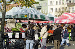 Outdoor farmers market, people buying food. Farmers market day outdoors with a bunch of people fruit and vegetable sellers. A lively scene with much expressions royalty free stock photography