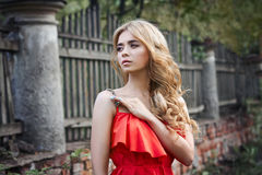 Outdoor fashion beautiful young woman photo near old HOMESTEAD summer. Portrait girl blondes in red dress. Royalty Free Stock Photo