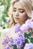 Outdoor fashion beautiful young woman surrounded by lilac flowers summer. Spring blossom lilac bush. Portrait of a girl blond. Es royalty free stock photo