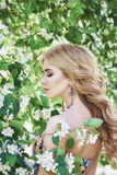 Outdoor fashion beautiful young woman surrounded by lilac flowers summer. Spring blossom lilac bush. Portrait of a girl blond Stock Images