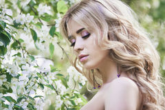 Outdoor fashion beautiful young woman surrounded by lilac flowers summer. Spring blossom lilac bush. Portrait of a girl blond. Es Stock Photo