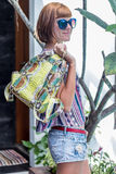 Outdoor fashion details, woman posing at the swimming pool, wearing luxury snakeskin python backpack, sunny bright Royalty Free Stock Photo