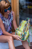 Outdoor fashion details, woman posing at the swimming pool, wearing luxury snakeskin python backpack, sunny bright Royalty Free Stock Photography