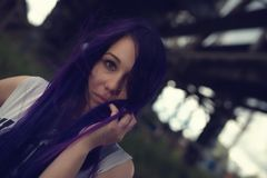 Outdoor fashion lifestyle portrait of pretty young girl, wearing in hipster swag grunge style with violet hair urban background Stock Images