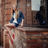 Outdoor fashion lifestyle portrait of pretty young sitting girl, wearing in hipster swag grunge style urban background stock images