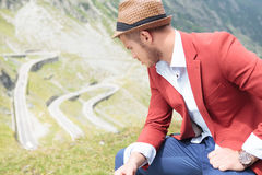 Outdoor fashion man sits and looks down Royalty Free Stock Photos