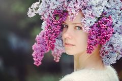 Outdoor fashion photo of a beautiful young blue-eyed woman. Spring color. beautiful blonde girl in lilac flowers. Perfume with a s. Cent of flowers. Perfumes and royalty free stock photos