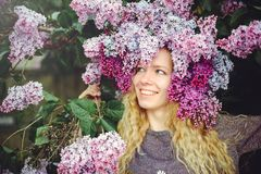 Outdoor fashion photo of a beautiful young blue-eyed woman. Spring color. beautiful blonde girl in lilac flowers. Perfume with a s. Cent of flowers. Perfumes and royalty free stock photo